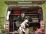 Man sitting in van boot holding lamb