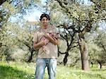 Man holding a piglet in field on farm