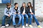 Groupe d'amis assis sur un banc, à l'extérieur