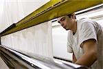 Usine de tissu enduit, machinistes travaillant sur la ligne de production