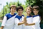 Junge Fußball-Teamkollegen Trophäe zusammenhalten, portrait