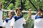 Garçons sur le terrain de soccer, poings soulevées dans la victoire