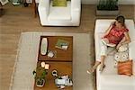 Frau entspannen auf Sofa mit Buch auf Schoß, Gespräch am Handy