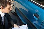 Expert en sinistres examinant les dommages à l'extérieur de la voiture