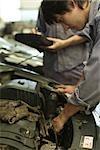 Mechanics repairing car engine