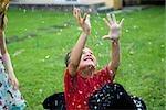 Garçon avec bras levés douché en confettis tombant