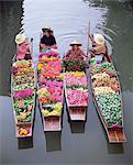 Un groupe de quatre femmes marché des marchands de bateaux chargés de fruits et les fleurs, le marché flottant de Damnoen Saduak, Bangkok, Thaïlande, Asie du sud-est, Asie