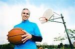 Mann mit Basketball am Basketballplatz