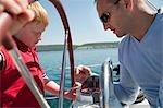 Man explaining boy compass on yacht