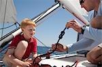 Man teaching boy knot on yacht