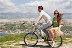 Couple riding bike by sea