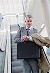 Businessman descending escalator and checking the time