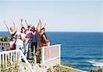 Friends cheering on patio near ocean