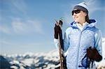 Woman on mountain holding skis