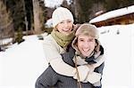 Man giving girlfriend piggyback ride in snow