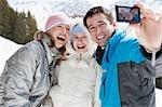 Family taking self-portrait in snow