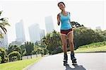 Femme patin à roues alignées dans le parc urbain