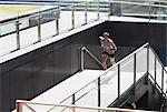 Man running up urban staircase