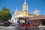 Horse cart passing Cathedral de Granada, Park Colon (Park Central), Granada, Nicaragua, Central America