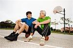 Vater und Sohn sitzen auf Basketbälle auf Platz