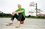 Man Sitting on Basketball on Court