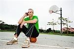 Mann mit Handy auf Basketballplatz