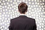 Homme d'affaires en regardant un mur plein d'auto adhésif note