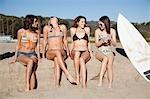 Young Women with Surfboard Sitting on Beach, Zuma Beach, California, USA