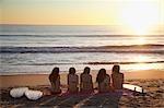 Backview des jeunes femmes avec des planches de surf, assis sur la plage en regardant le coucher du soleil, Zuma Beach, Californie, USA