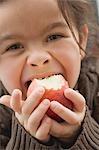 Girl biting into an organic apple