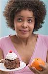 Jeune femme indécise entre le gâteau et orange