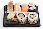 Assortiment sushi dans une boîte en plastique avec la sauce de soja & de gingembre