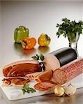 Smoked ham, bologna sausage and salami on chopping board