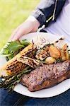 Femme tenant un plat de bœuf, légumes grillés & maïs en épi