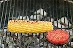 Cob of corn and tomato on a barbecue