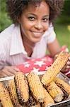 Femme prenant le maïs grillé en épi de plat en aluminium