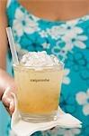 Femme tenant un cocktail en verre avec le mot « Caipirinha »