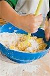 Kind Ei mit Mehl und Butter in einer Schüssel mischen