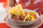 Frau mit Chili Con Carne mit Nachos und Paprika
