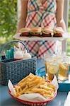 Chips und Eistee auf Tisch, Frau Hamburger servieren