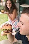 Paar Essen Hamburger auf Terrasse