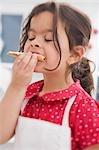 Petite fille manger des biscuits de Noël qu'elle a fait elle-même