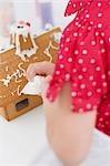 Small girl decorating gingerbread house using piping bag