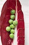 Several peas on radicchio leaf