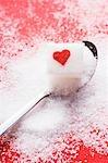 Cube de sucre avec un coeur rouge sur la cuillère