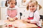 Zwei kleine Mädchen kneten Teig