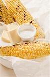 Maïs grillé en épi avec le sel et les morceaux de beurre
