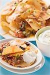 Tortilla Chips mit geschmolzenem Käse, Oliven und Sauerrahm