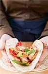 Hands folding a chicken-filled tortilla