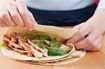 Folding a tortilla over chicken filling